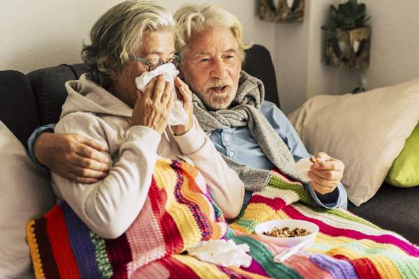 Couple of old aged senior people at home with seasonal winter cold illness disease  sit down on the sof together forever - health problems for retired man and woman with white hair
